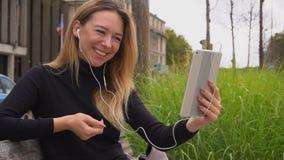 Kvinna som talar vid minnestavlan och i öratelefoner med videopp appeller som sitter på bänk och visar tummar upp i ultrarapid lager videofilmer