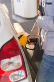 Kvinna som tankar bilbehållaren och den hållande plånboken fotografering för bildbyråer