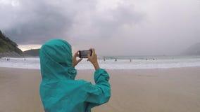 Kvinna som tar bilden med den smarta telefonen på Nai-harnstranden lager videofilmer