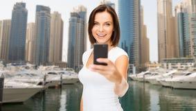 Kvinna som tar bilden vid smartphonen över den dubai staden royaltyfri fotografi