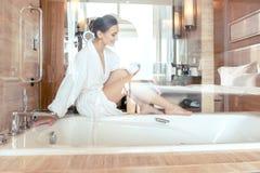 Kvinna som tar bort hår, genom att raka henne ben i badrum av hotellet royaltyfri foto
