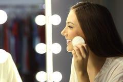 Kvinna som tar bort smink i en spegel Royaltyfri Foto
