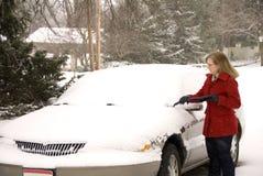 Kvinna som tar bort Snow från bil 1 Arkivbild
