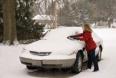 Kvinna som tar bort Snow från bil 3 Arkivfoto
