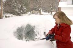 Kvinna som tar bort Snow från bil 6 Royaltyfria Bilder