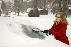 Kvinna som tar bort Snow från bil 9 Arkivfoton