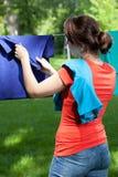 Kvinna som tar bort tvätterit från klädstreck arkivfoto