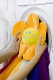 Kvinna som tar den fluffiga leksaken från tvagningmaskinen Royaltyfri Foto