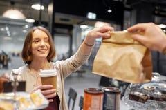 Kvinna som tar den pappers- påsen från säljare på kafét Fotografering för Bildbyråer