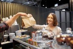 Kvinna som tar den pappers- påsen från säljare på kafét Royaltyfria Bilder