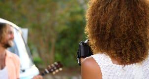 Kvinna som tar en bild av en man som spelar gitarren stock video