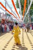 Kvinna som tar en gå och iklädda gula traditionella dräkter på den Seville `en s April Fair Arkivbild