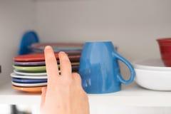 Kvinna som tar en kopp från ett köksskåp för frukost arkivfoton