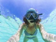 kvinna som tar en undervattens- selfie, medan snorkla i kristallklart tropiskt vatten royaltyfria foton