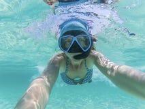 kvinna som tar en undervattens- selfie, medan snorkla i kristallklart tropiskt vatten royaltyfri foto