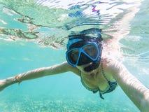 kvinna som tar en undervattens- selfie, medan snorkla i kristallklart tropiskt vatten royaltyfria bilder