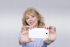 Kvinna som tar ett foto Fotografering för Bildbyråer