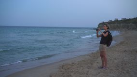 Kvinna som tar ett foto av ett hav p? den smarta telefonen p? solnedg?ng arkivfilmer