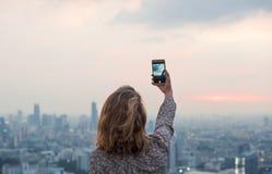 Kvinna som tar ett foto av solnedgången arkivfoto