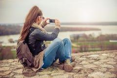 Kvinna som tar ett foto med mobiltelefonen arkivfoto