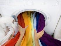 Kvinna som tar färgtvätterit från tvagningmaskinen Royaltyfri Foto