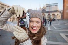 Kvinna som tar foto med den retro fotokameran på piazza San Marco Arkivbilder