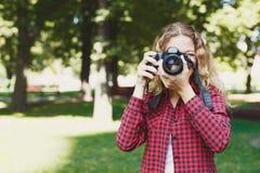 Kvinna som tar foto, medan stå i parkera royaltyfri fotografi