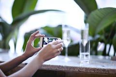Kvinna som tar fotoet av champagneexponeringsglas Möte i stadsrestaurang eller kafé houseplants Royaltyfri Bild