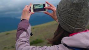 Kvinna som tar fotografismartphonen som delar fotoet av landskapnaturbakgrund som tycker om semesterferielopp arkivfilmer