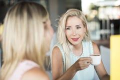 Kvinna som tar konversation, medan dricka kaffe arkivfoton