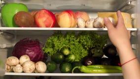 Kvinna som tar mat från kylskåpet arkivfilmer