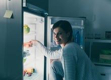 Kvinna som tar mat ut ur kylen arkivfoto