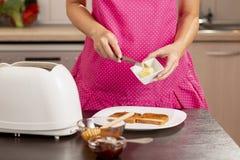 Kvinna som tar något smör för en smörgås royaltyfri foto