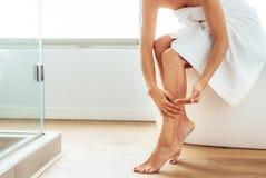 Kvinna som tar omsorg av hennes kropp efter bad arkivbild