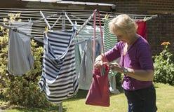 Kvinna som tar pinnor från en pinnepåse till hängningtvagningen Arkivfoto