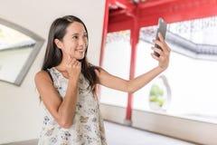 Kvinna som tar selfie i kinesträdgård royaltyfri bild