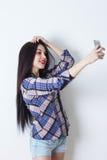Kvinna som tar selfie med hennes smartphone Fotografering för Bildbyråer