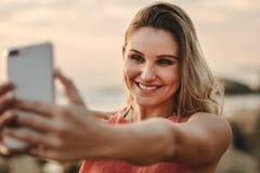 Kvinna som tar selfie som står på stranden royaltyfria foton