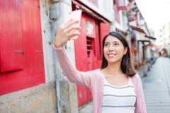 Kvinna som tar selfie vid den smarta telefonen i Rua da felicidade Royaltyfri Fotografi