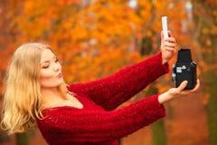 Kvinna som tar självfotoet med två moderna kameror som är retro och Arkivfoton