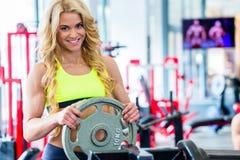 Kvinna som tar vikter från ställning i konditionidrottshall Royaltyfria Bilder