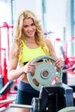 Kvinna som tar vikter från ställning i konditionidrottshall Arkivfoton