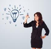 Kvinna som tecknar den ljusa kulan på whiteboard arkivfoton