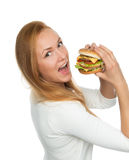 Kvinna som äter den smakliga sjukliga hamburgareostburgaresmörgåsen Arkivfoto