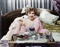 Kvinna som äter frukosten i säng (alla visade personer inte är längre uppehälle, och inget gods finns Leverantörgarantier som där Arkivfoto