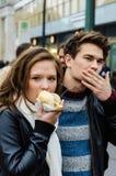 Kvinna som äter hotdogen medan manlokalvårdmun Arkivfoton