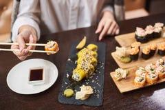 Kvinna som ?ter och tycker om den nya sushi i lyxig restaurang fotografering för bildbyråer