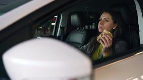 Kvinna som ?ter sm?rg?sen som sitter i bilen p? parkeringen Begrepp av ett modernt upptaget liv lager videofilmer