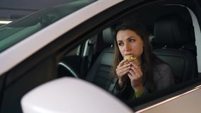 Kvinna som ?ter sm?rg?sen som sitter i bilen p? parkeringen Begrepp av ett modernt upptaget liv arkivfilmer