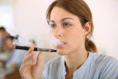 Kvinna som testar den elektroniska cigaretten Arkivbild